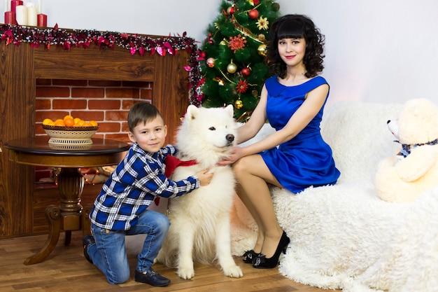 Eine junge mutter mit ihrem sohn und einem hund an einem weihnachtsbaum.