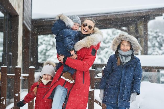 Eine junge mutter mit ihren baumkindern hat spaß und spielt schneebälle im freien in der nähe des hauses.