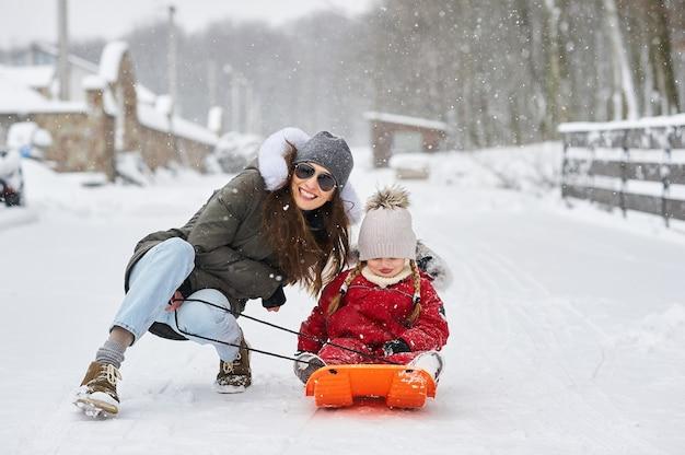 Eine junge mutter mit ihren kindern, die spaß im winter haben