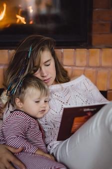 Eine junge mutter und ein sohn lesen in der nähe des kamins ein märchenbuch.
