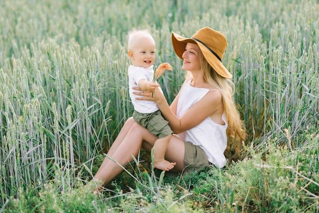 Eine junge mutter und ihr kleines kind, die nahe dem weizen auf einem grünen hintergrund sitzen