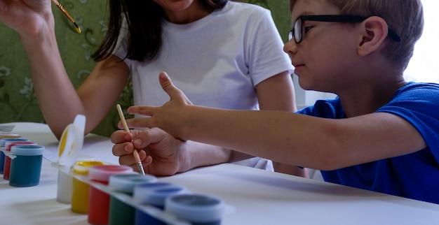 Eine junge mutter und sein süßer kleiner sohn in gläsern zeichnen zusammen mit farben auf weißem papier.