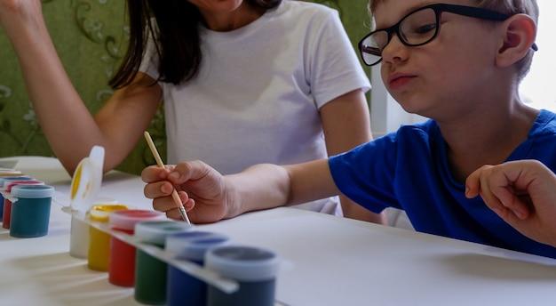 Eine junge mutter und sein süßer kleiner sohn zeichnen und malen zusammen auf weißem papier.