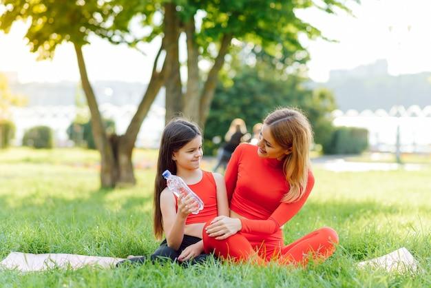 Eine junge mutter und tochter in sportbekleidung machen zusammen yoga in einem park