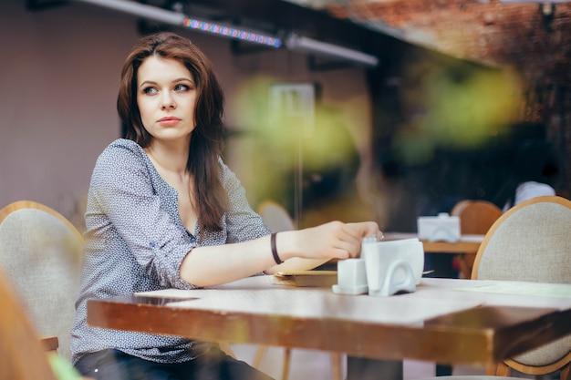 Eine junge nachdenkliche frau träumt in erwartung einer wartezeit von etwas