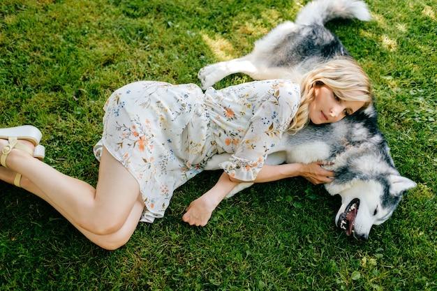 Eine junge romantische frau, die mit einem glücklichen hund auf dem gras liegt