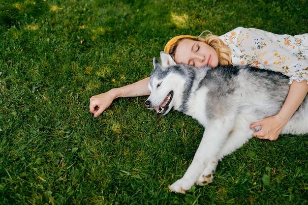 Eine junge romantische frau, die mit einem hund auf dem gras liegt