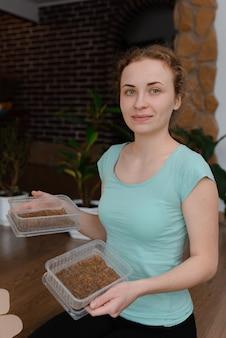 Eine junge rothaarige frau, die einen behälter mit gepflanzten microgreens hält. hausgartenarbeit