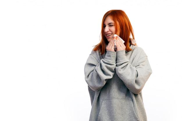 Eine junge rothaarige frau in einem grauen sweatshirt wurde mit einem griff und niesen krank