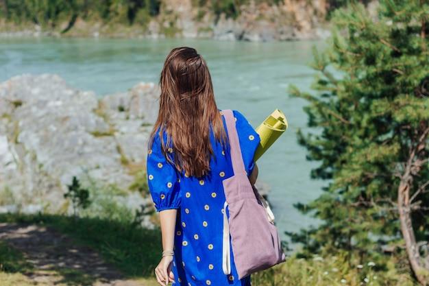 Eine junge schlanke brünette frau in einem blauen ethnischen kleid geht zu spirituellen praktiken in der natur