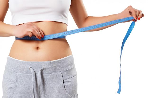 Eine junge schlanke frau misst ihre taille mit einem zentimeterband.