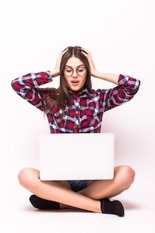 Eine junge schockierte frau, die auf dem boden mit einem laptop auf weiß sitzt