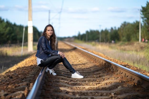 Eine junge schöne alleinstehende frau sitzt an einem klaren sommertag auf den bahngleisen und wartet auf eine lokomotive