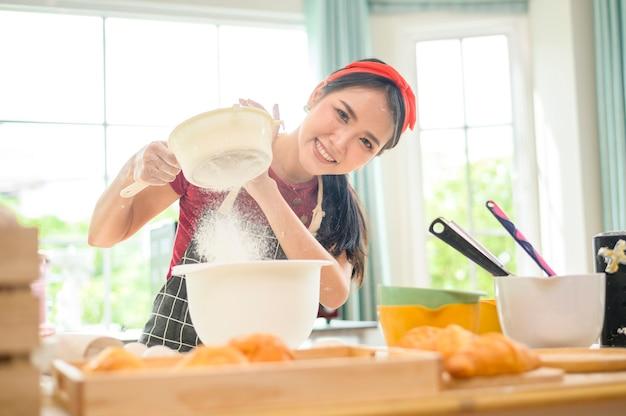 Eine junge schöne asiatin backt in ihrem küchen-, bäckerei- und café-geschäft