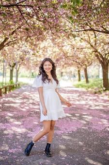 Eine junge schöne asiatische frau in einem weißen kleid geht in einem blumenpark. sakura. blühende bäume. frühling.