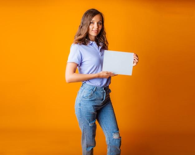Eine junge schöne blondine in blauem t-shirt und jeans hält ein weißes blatt papier in den händen. platz kopieren.