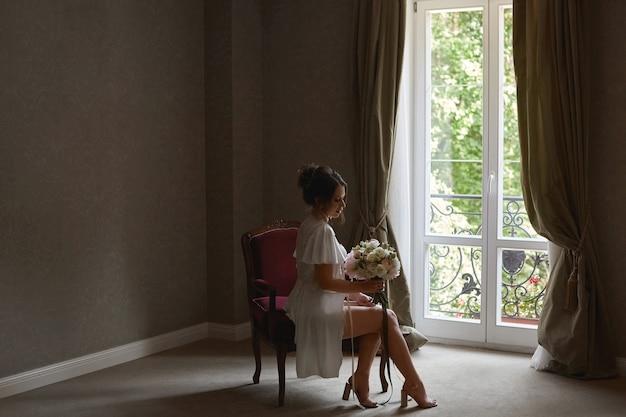 Eine junge schöne braut im seidenkleid hält hochzeitsblumenstrauß und sitzt auf dem stuhl in einem hotelzimmer
