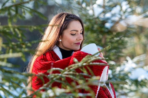 Eine junge, schöne brünette mit einem roten plaid auf der schulter und einer tasse tee in den händen im wald zwischen den schneebedeckten weihnachtsbäumen