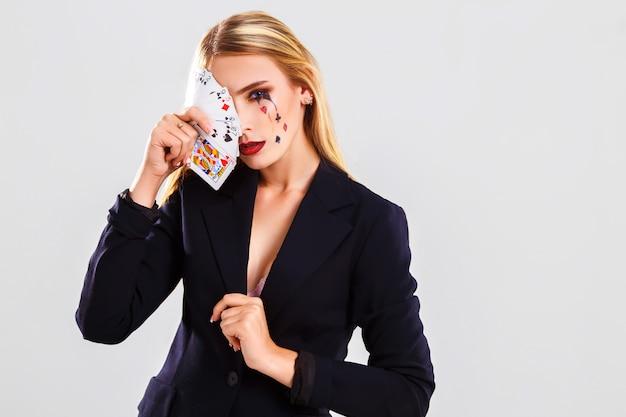 Eine junge schöne dame croupier. glücksspiel- und casino-konzept. studioaufnahme. weißer hintergrund .
