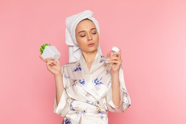 Eine junge schöne dame der vorderansicht im bademantel, der pflanze und flasche hält