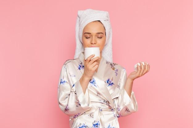 Eine junge schöne dame der vorderansicht im bademantel, die gesichtscreme hält
