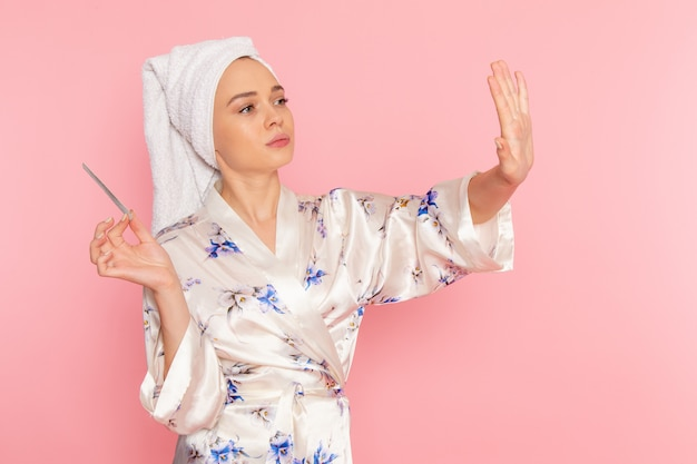 Eine junge schöne dame der vorderansicht im bademantel, die ihre nägel repariert