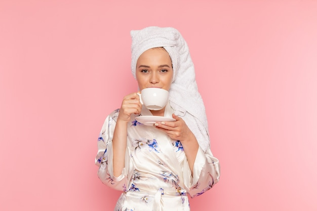 Eine junge schöne dame der vorderansicht im bademantel, die kaffee mit lächeln auf ihrem gesicht trinkt