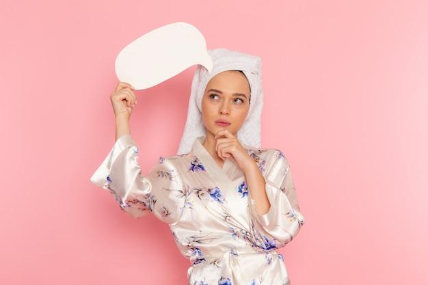 Eine junge schöne dame der vorderansicht im bademantel, die weißes zeichen denkt und hält