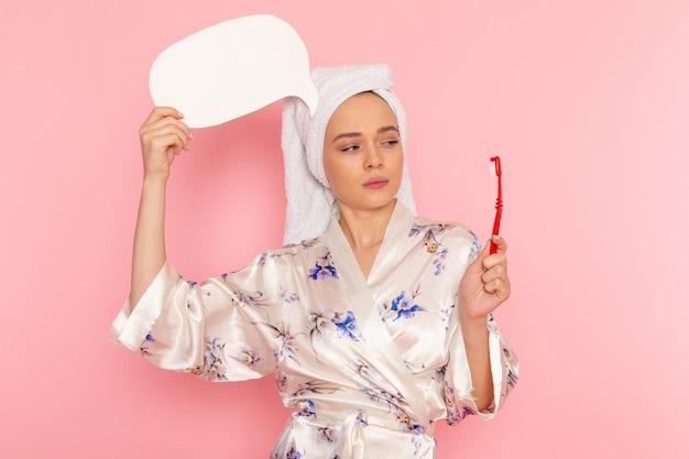 Eine junge schöne dame der vorderansicht im bademantel, die weißes zeichen und zahnbürste hält