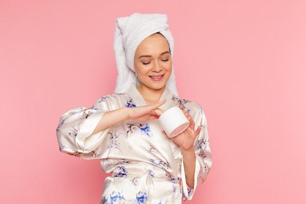 Eine junge schöne dame der vorderansicht im bademantel unter verwendung einer gesichtscreme