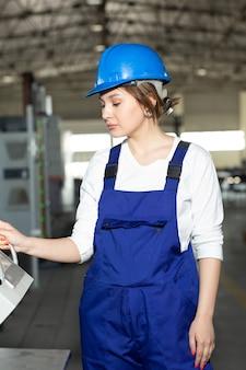 Eine junge schöne dame der vorderansicht im blauen bauanzug und in den helm, die maschinen im hangar steuern, die während der architektur des tagesgebäudes arbeiten