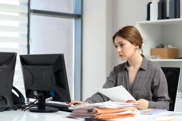 Eine junge schöne dame der vorderansicht im grauen hemd, das mit den dokumenten und dem laptop arbeitet, die in ihrem büro während der tagesaufbauarbeitstätigkeit sitzen
