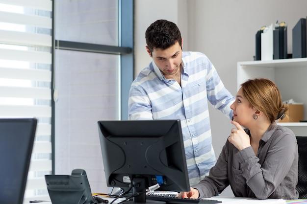 Eine junge schöne dame der vorderansicht im grauen hemd, die etwas mit dem jungen mann im büro während der tagesaufbaujobaktivität spricht und bespricht