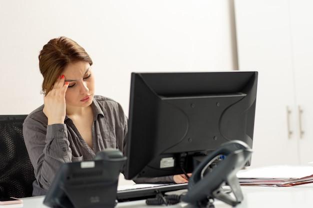 Eine junge schöne dame der vorderansicht im grauen hemd, die ihren pc verwendet, der in ihrem büro sitzt und denkt, während des tagesaufbaus jobaktivität zu berechnen