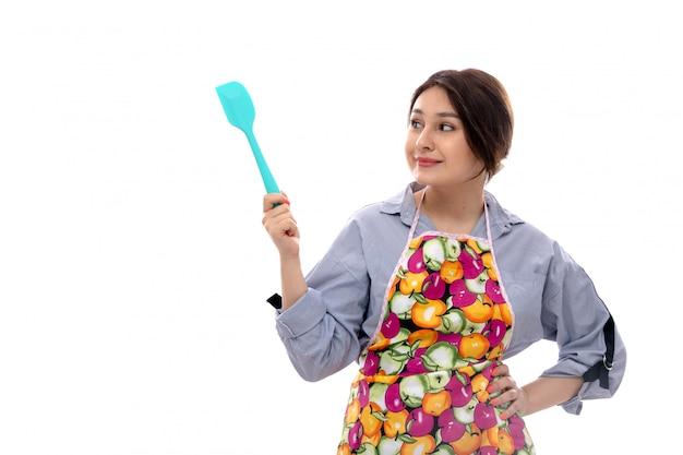 Eine junge schöne dame der vorderansicht im hellblauen hemd und im bunten umhang denken, das blaues küchengerät lächelnd hält