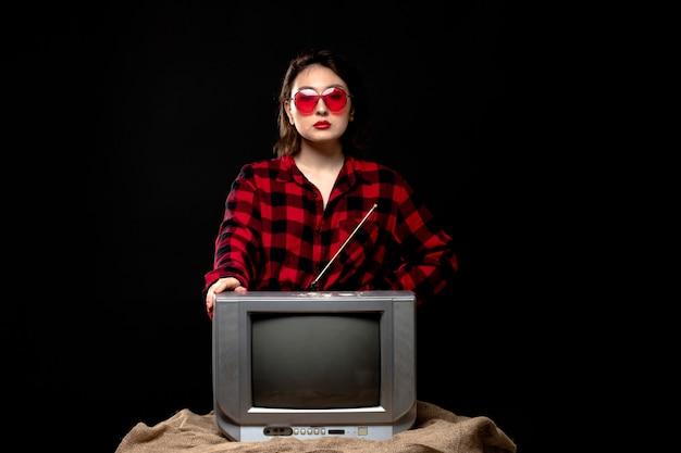 Eine junge schöne dame der vorderansicht im karierten rot-schwarzen hemd in der roten sonnenbrille nahe dem kleinen fernseher