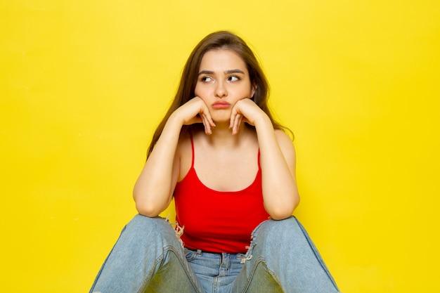 Eine junge schöne dame der vorderansicht im roten hemd und in den blauen jeans, die mit unzufriedenem ausdruck aufwerfen