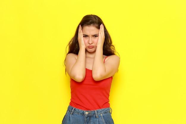 Eine junge schöne dame der vorderansicht im roten hemd und in den blauen jeans, die mit verrücktem ausdruck aufwerfen