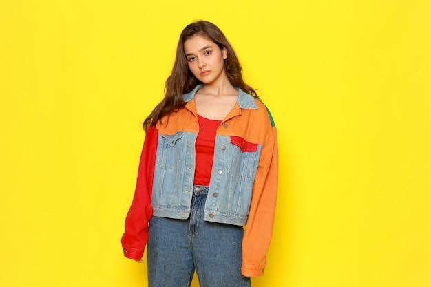 Eine junge schöne dame der vorderansicht im roten hemdmantel und in den gerade stehenden blauen jeans