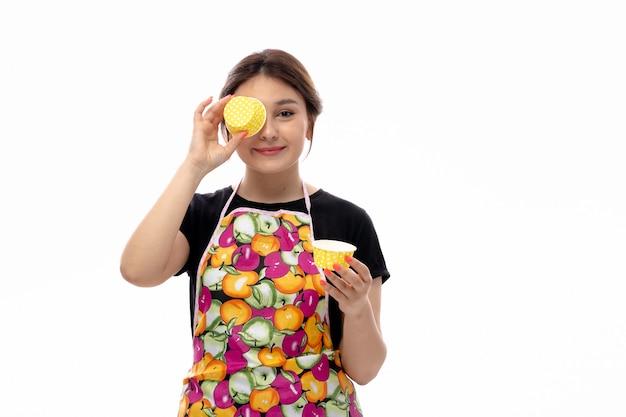 Eine junge schöne dame der vorderansicht im schwarzen hemd und im bunten umhang, der gelbe kleine kuchenformen hält, die lächelnd ihr auge bedecken