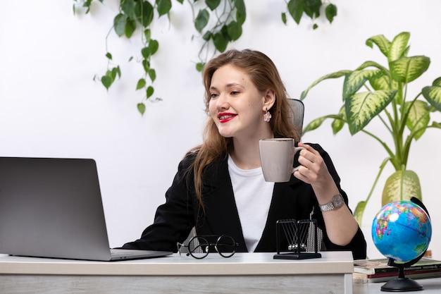 Eine junge schöne dame der vorderansicht im weißen hemd und in der schwarzen jacke, die ihren laptop vor dem lächelnden halten der tasse des tisches mit hängenden blättern verwendet