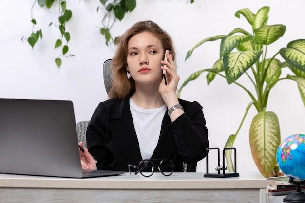 Eine junge schöne dame der vorderansicht im weißen hemd und in der schwarzen jacke, die ihren laptop vor dem tisch verwendet, der am telefon mit hängenden blättern spricht