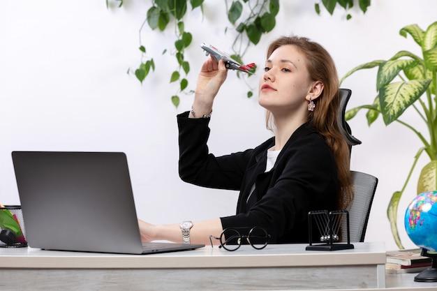 Eine junge schöne dame der vorderansicht im weißen hemd und in der schwarzen jacke unter verwendung ihres laptop, der spielzeugflugzeug vor tisch mit hängenden blättern hält