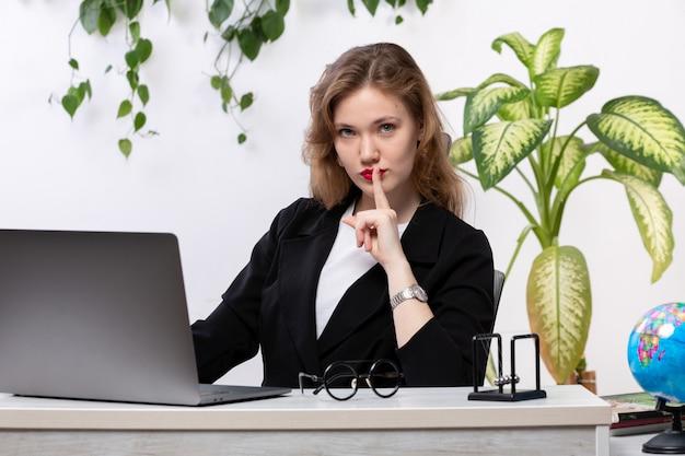 Eine junge schöne dame der vorderansicht im weißen hemd und in der schwarzen jacke unter verwendung ihres laptops vor dem lächelnden tisch, das schweigenzeichen mit hängenden blättern zeigt