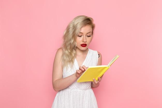 Eine junge schöne dame der vorderansicht im weißen kleid, das ein heft liest