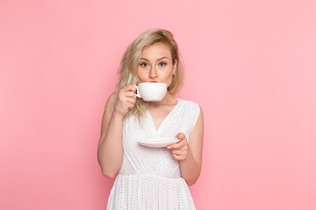 Eine junge schöne dame der vorderansicht im weißen kleid, das einen tee trinkt
