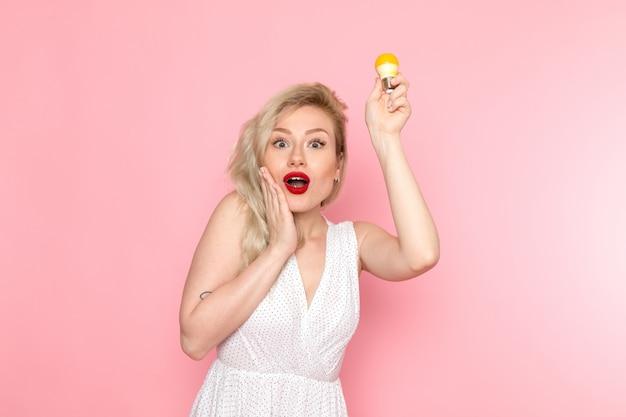 Eine junge schöne dame der vorderansicht im weißen kleid, das gelbe glühbirne hält