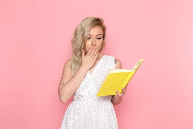 Eine junge schöne dame der vorderansicht im weißen kleid, das gelbes heft hält
