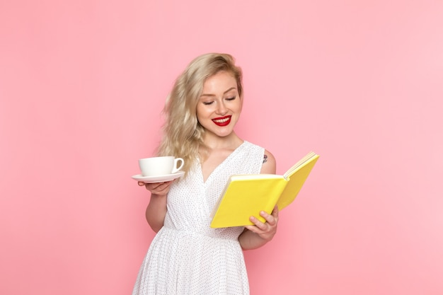 Eine junge schöne dame der vorderansicht im weißen kleid, das heft und tasse tee mit lächeln auf ihrem gesicht hält