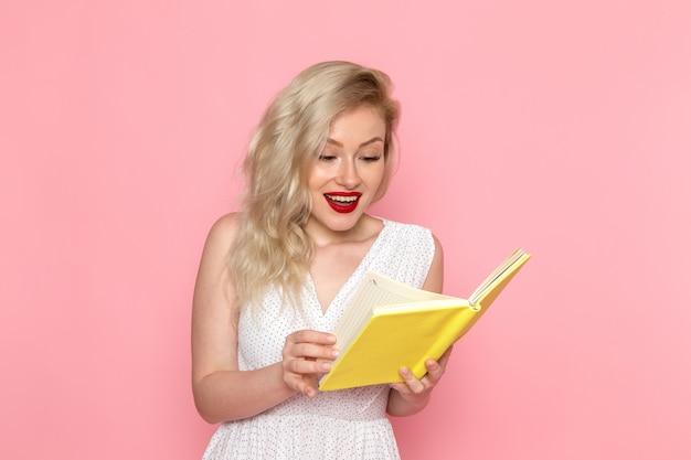 Eine junge schöne dame der vorderansicht im weißen kleid, die ein heft mit einem lächeln auf ihrem gesicht liest